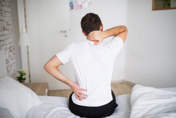 Literie Dijon, Homme de dos, se levant de son lit avec un mal de dos